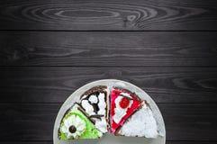 不同的蛋糕在一块板材的在黑暗的木背景 库存图片