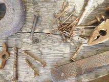 不同的钉子和铜丝在一木bacground 库存图片