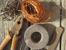 不同的钉子和铜丝在一木bacground 库存照片