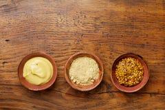 不同的集香料 法国芥末、第茂芥末和粉末在木土气台式视图 库存照片