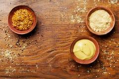 不同的集香料 法国芥末、第茂芥末和粉末在木土气桌顶上的视图 库存照片