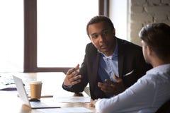 不同的雇员在办公室谈判打手势在膝上型计算机附近 免版税库存照片