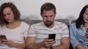 不同的青年人在行坐被设备一起占据心思的长沙发网上,白种人上瘾者使用他们 股票录像