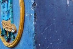 不同的音调难看的东西抽象背景蓝色墙壁与压印的黄色插入物的以在左边的一个圈子的形式 免版税图库摄影