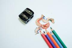 不同的颜色一些色的铅笔和刮在白皮书背景的铅笔刀和铅笔 免版税库存照片
