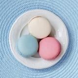 不同的颜色和不同的口味在一块白色板材,顶视图三个蛋白杏仁饼干  方形背景 库存照片