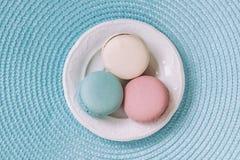 不同的颜色和不同的口味在一块白色板材,顶视图三个蛋白杏仁饼干  浪漫早晨,心爱的礼物 免版税库存照片