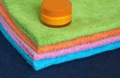不同的颜色在棉花背景的毛巾和奶油 免版税库存照片