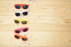 不同的颜色太阳镜在木地板上的 库存图片