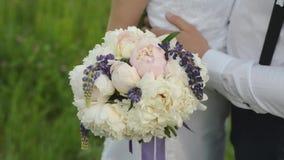 不同的颜色美丽的花束在新娘的手上一件白色礼服的 与婚礼的愉快的已婚夫妇 股票录像