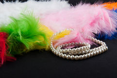 不同的颜色羽毛和perl项链在黑背景放置 免版税库存照片