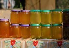 不同的颜色蜂蜜在同一块玻璃的在市场上刺激 射击户外 图库摄影