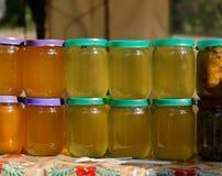 不同的颜色蜂蜜在同一块玻璃的在市场上刺激 射击户外 库存照片