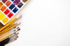 不同的颜色水彩油漆与各种各样的刷子的 库存照片