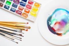 不同的颜色水彩油漆与各种各样的刷子的 免版税库存图片