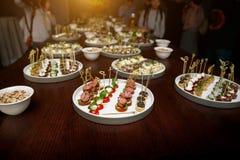 不同的食物快餐和开胃菜在圆的板材在公司事件集会 与承办酒席宴会桌的庆祝 免版税库存图片