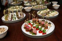 不同的食物快餐和开胃菜在圆的板材在公司事件集会 与承办酒席宴会桌的庆祝 图库摄影