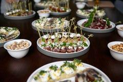 不同的食物快餐和开胃菜在圆的板材在公司事件集会 与承办酒席宴会桌的庆祝 免版税图库摄影