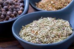 不同的香料和草本在匙子或碗在木的褐色 免版税库存照片