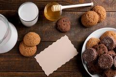 不同的鲜美曲奇饼用蜂蜜和牛奶在一张棕色木桌上 在视图之上 免版税库存照片