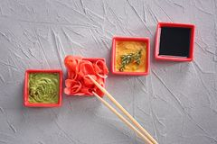 不同的鲜美调味汁用在碗的用卤汁泡的姜在灰色背景 库存图片