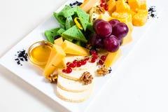不同的类乳酪,切的,红葡萄,核桃,在碗的蜂蜜,红浆果,绿色乳酪,木立场 免版税库存图片