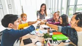 不同种族的不同的小组办公室工友,商务伙伴拳头爆沸在现代办公室 同事合作配合概念 免版税库存照片