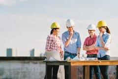 不同种族的不同的小组工程师或商务伙伴建造场所的,在大厦` s图纸 免版税图库摄影