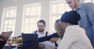 不同种族的专业软件开发商与膝上型计算机一起运作在顶楼办公室桌上 Hackathon事件讨论 股票录像