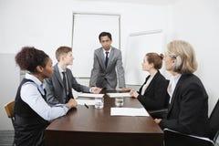 不同种族的买卖人在会议上在会议室 免版税库存图片