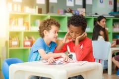 不同种族的基本的学生阅读书行在教室 葡萄酒作用样式图片 图库摄影