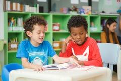不同种族的基本的学生阅读书行在教室 免版税库存图片