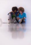 不同种族的夫妇坐与膝上型计算机和片剂的地板 免版税库存图片