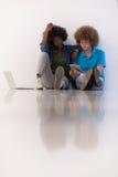 不同种族的夫妇坐与膝上型计算机和片剂的地板 免版税图库摄影