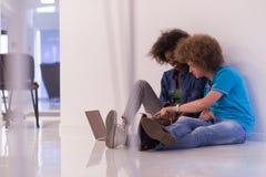 不同种族的夫妇坐与膝上型计算机和片剂的地板 库存照片