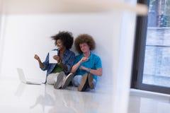 不同种族的夫妇坐与膝上型计算机和片剂的地板 库存图片