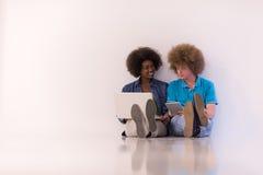 不同种族的夫妇坐与膝上型计算机和片剂的地板 免版税库存照片