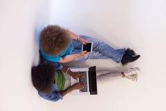不同种族的夫妇坐与膝上型计算机和片剂的地板 图库摄影
