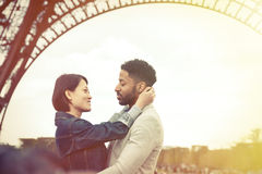 不同种族的夫妇获得乐趣在巴黎在艾菲尔铁塔附近 免版税库存照片