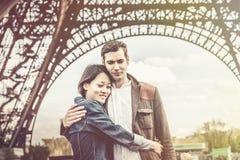 不同种族的夫妇获得乐趣在巴黎在艾菲尔铁塔附近 免版税库存图片
