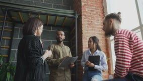不同种族的学生队是群策群力和谈论新的想法在现代教室在大学,当站立时 股票录像