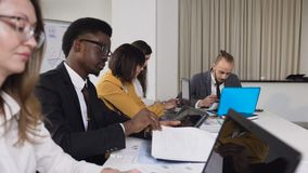 不同种族的小组年轻商人在桌上坐会议在候选会议地点 一个小组混杂 股票视频