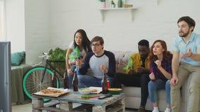 不同种族的小组朋友有巴西旗子的体育迷一起观看在电视的橄榄球冠军在家和 股票视频