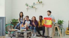 不同种族的小组朋友有西班牙旗子的体育迷一起观看在电视的橄榄球冠军在家和 股票录像