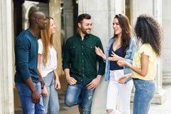 不同种族的小组朋友获得乐趣一起在都市backg 免版税库存照片