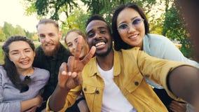 不同种族的小组青年人非裔美国人,亚洲人和白种人采取在野餐的selfie与饮料看 影视素材