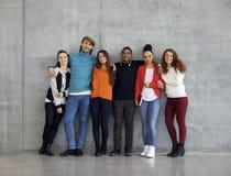 不同种族的小组在校园里的愉快的年轻大学生 免版税库存照片