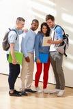 不同种族的小组学生在有数字式片剂的教室 免版税库存图片