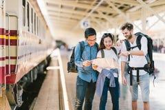 不同种族的小组朋友、背包旅客或者一起使用地方地图航海的大学生在火车站 免版税库存照片