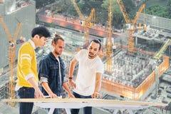 不同种族的工程师,建筑师队一起研究大厦发展规划计划,建设中站点背景 库存照片